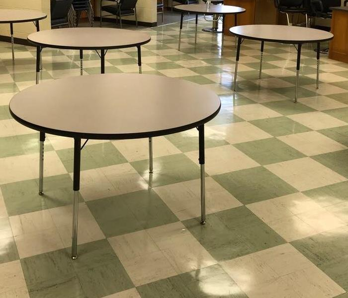 Dried Tile Flooring In Conference Area With Chairs Removed From Tables On Floor.