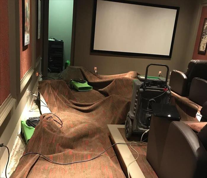 Entertaining Area With Movie Seating Flooded Affecting The Carpets In The Room. SERVPRO Equipment In Use On Floors.