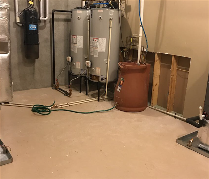 Dried And Restored Flooded Basement Around Hot Water Heaters In Corner.