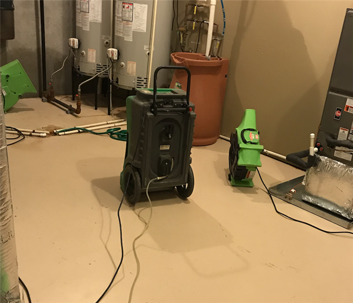 Basement Flooded Around Hot Water Heaters In Corner Of Room With SERVPRO Equipment In Use On Floor.