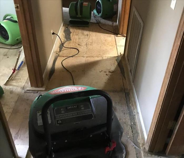 SERVPRO equipment sitting in hallway of a home that has faced water damage to their flooring.