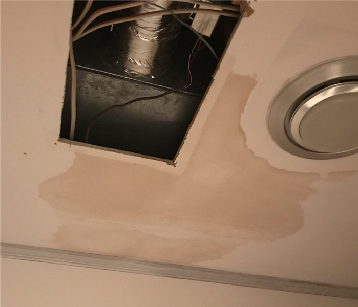 Water damage on ceiling causing discoloration at local business.