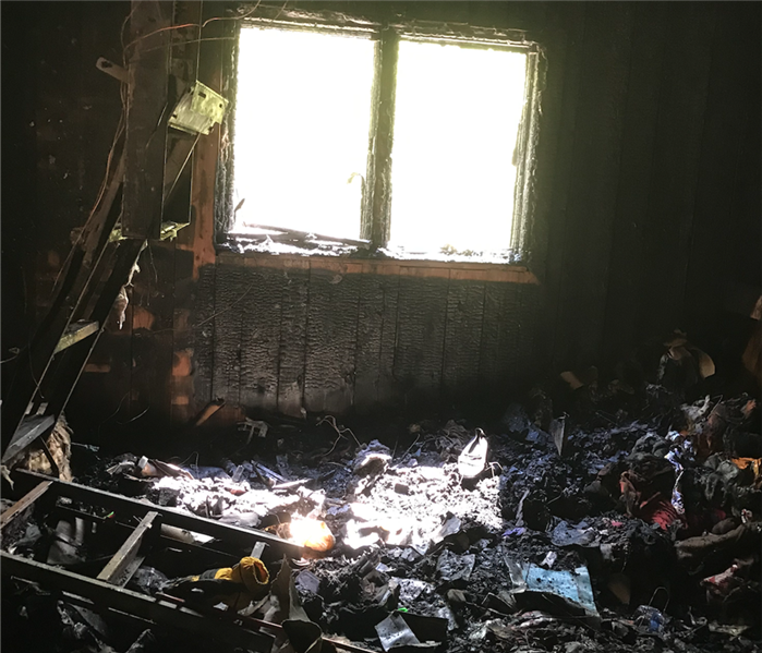 Living room that has been burned in a house fire with black soot on walls and on belongings.