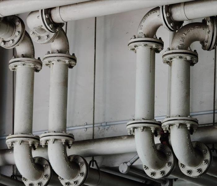 White piping system running together along a wall inside a building.